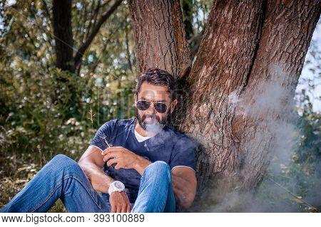 Bearded Smoker Enjoying An Electronic Cigarette In The Calm Outdoors. Hybrid Cigarette.
