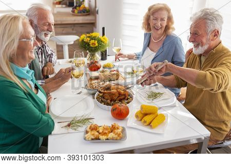 Senior Friends Celebrating Thanksgiving Together At Home Over Traditional Dinner, Host Cutting The C