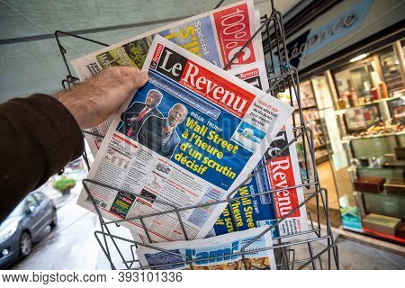 Paris, France - Nov 3, 2020: Pov Male Hand At The Le Revenu French Newspaper With Cover Featuring Fi