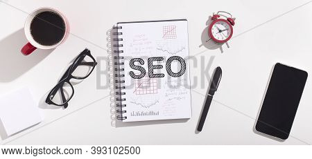 Word Seo On Opened Notebook Over White Office Table Background With Smartphone And Supplies. Interne