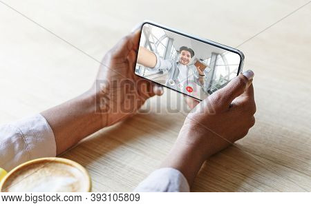 Unrecognizable Black Woman Drinking Coffee And Having Videocall With Her Caucasian Boyfriend, Using