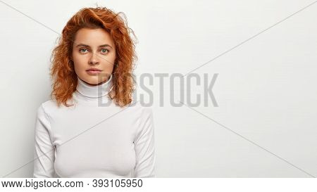 Photo Of Serious Beautiful Ginger Woman With Green Eyes, Smooth Healthy Skin, Has Red Wavy Natural H