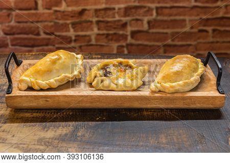Traditional Baked Argentine And Uruguay Empanadas Savoury Pastries With Meat Beef Stuffing Against W