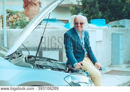 Business Man, Happy Driver Sitting On His Car With Opened Hood Showing The Car Engine Carburetor Smi