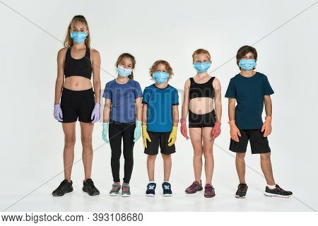 Full Length Shot Of Five Sportive Kids In Sportswear Wearing Medical Masks And Gloves Looking At Cam