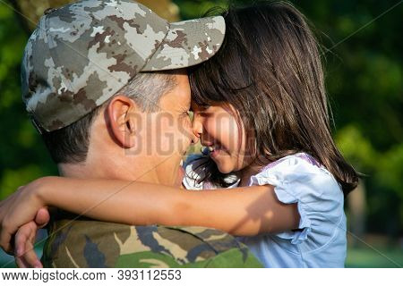 Cheerful Military Dad Holding Little Daughter In Arms, Hugging Girl Outdoors After Returning From Mi