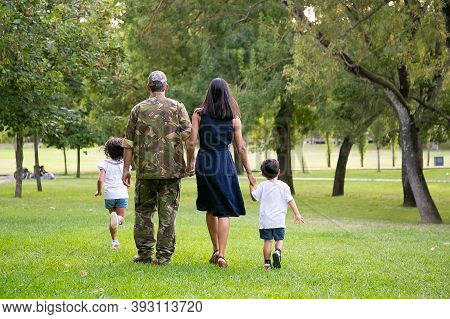 Military Man Walking In Park With His Wife And Children, Kids And Parents Holding Hands. Full Length
