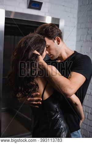 Passionate Man Embracing Sexy Woman, While Touching Curly Hair On Blurred Background