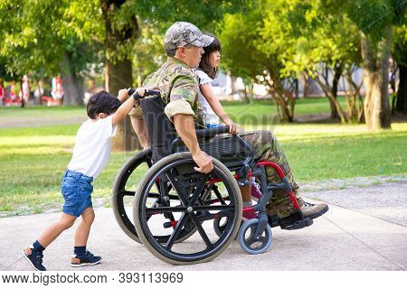 Disabled Retired Military Man Walking With Children In Park. Girl Sitting On Dads Lap, Boy Pushing W