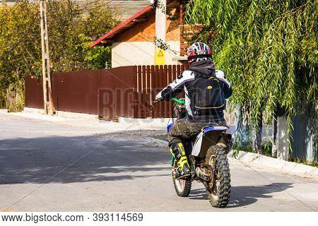Backview Of Rider On His Enduro Motorbike On A Village Road Near Targoviste, Romania, 2020