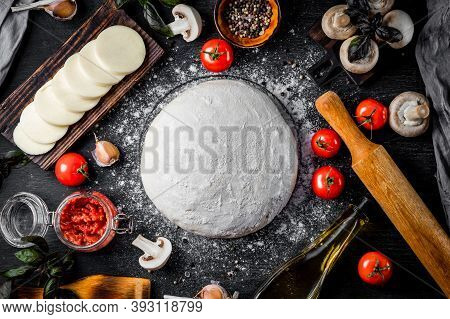 Ingredients For Making Pizza Dough, Mozzarella Cheese, Tomatoes, Mushrooms, Olive Oil And Basil On A