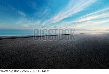 Panoramic Bright Skyline And Clouds With Empty Space Dark Concrete Asphalt Paved Road.  Sunrise Over