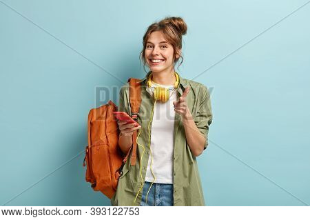 Photo Of Delighted European Woman Points At You Happily, Holds Smartphone Device Connected To Headph