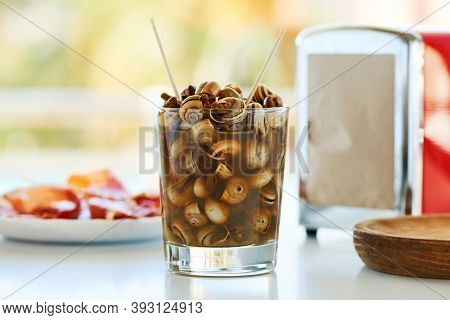 closeup of a glass with caracolillos en caldo, a spanish recipe of small snails cooked and served in broth typical of andalusia, next to a plate of serrano ham on a table