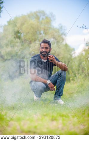Stylish Bearded Man With Electronic Cigarette On The Grass. Electronic Cigarette Concept.