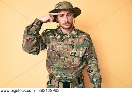 Young caucasian man wearing camouflage army uniform pointing unhappy to pimple on forehead, ugly infection of blackhead. acne and skin problem