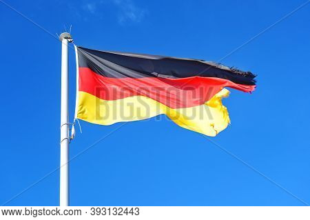 German Flag With Stripes In Black, Red, Gold On A Pole, Is Fluttering With Frayed Seam In The Wind A