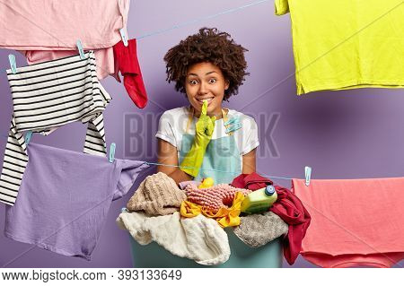 Laundry, Cleanliness And Housekeeping. Glad Housewife In Apron And Rubber Gloves, Makes Silence Gest