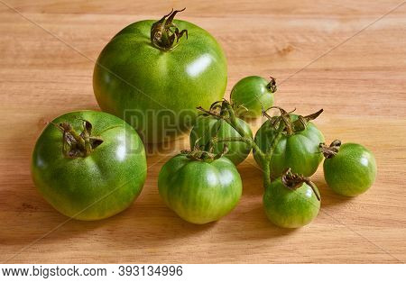 Green Unripe Tomatoes On A Wooden Background. Space For Text.