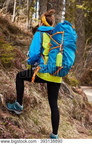 Photo Of Active Female Tourist Climbs On Hill Of Mountains, Carries Big Rucksack, Wears Boots, Enjoy