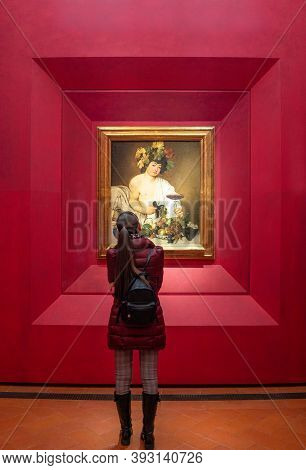 Florence, Italy - February 15, 2019: Uffizi Gallery, A Young Visitor Admires Thr Painting Of Bacchus