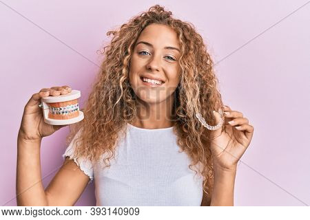Beautiful caucasian teenager girl holding invisible aligner orthodontic and braces smiling with a happy and cool smile on face. showing teeth.