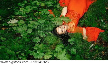 Fashionable Sexy Dark-haired Woman In A Red Long Dress Poses Lying In Nature Near The Grass. Long Cu