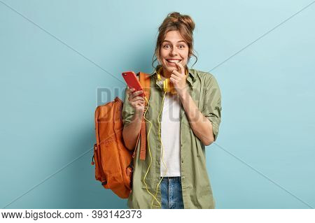 Delighted Pleased Woman Listens Audio In Electronic Headphones, Feels Good During Online Communicati