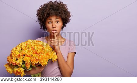 Horizontal Shot Of Secret Lovely Woman Keeps Fore Finger Over Lips, Tells Private Information To Clo