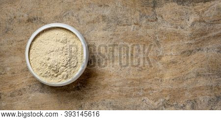 ashwagandha root (aka Indian ginseng) powder in a small ceramic bowl against handmade paper, superfood concept