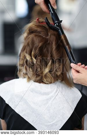 Woman In Beauty Salon Is Twisted Curls Of Hair On Curling Iron. Training For Masters In Evening And