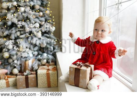 A Little Redhead Girl In A Christmas Costume In A Red Dress Sits On The Windowsill Near Christmas Tr