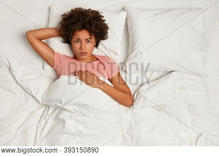 Photo From Above Of Afro American Woman Awakes In Angry Mood, Has Bad Dreams At Night, Stays In Bed