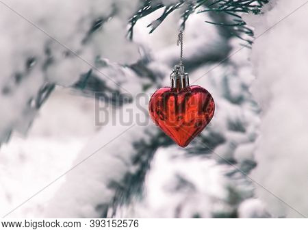 Christmas Background With Christmas Tree Toy Red Heart On Snow Covered Pine Branch In Winter Forest