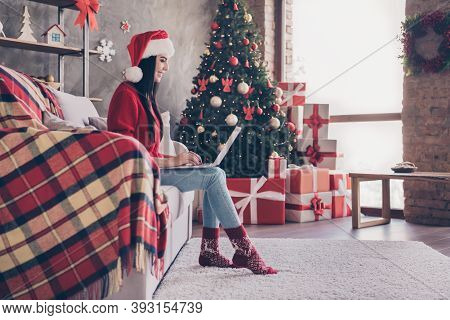 Photo Of Charming Young Lady Sit Couch Hold Netbook Wear Santa Cap Red Sweater Denim Jeans Socks In