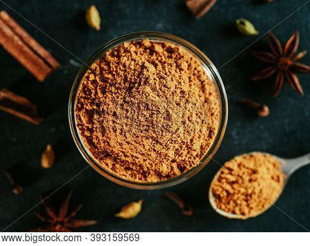 Indian Or Pakistani Masala Powder In Spoon And Small Glass Bowl. Close Up View Of Homemade Dry Curry