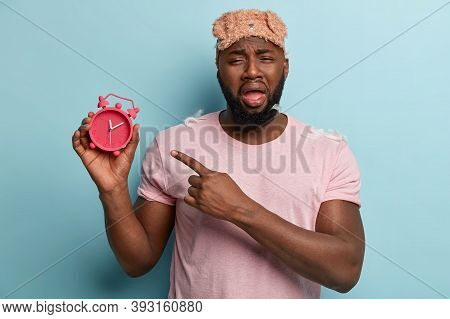 Frustrated Dejected Afro American Man Points With Miserable Expression At Alarm Clock, Wears Casual