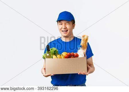 Online Shopping, Food Delivery And Shipment Concept. Winking Cute Asian Male Courier In Blue Uniform
