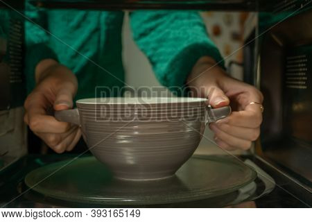 Women's Hands Take A Plate Out Of The Microwave, Photo From Inside