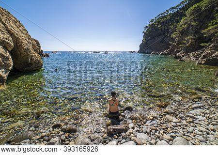 Pedrosa Cove With A Woman Sitting On The Seashore In Llafranc, Girona, Catalonia, Spain.