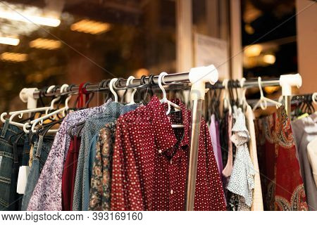 Shopping In Store. Colored Fashionable Clothes On Hangers In Street Shop For Sale. Discount Sale Ban
