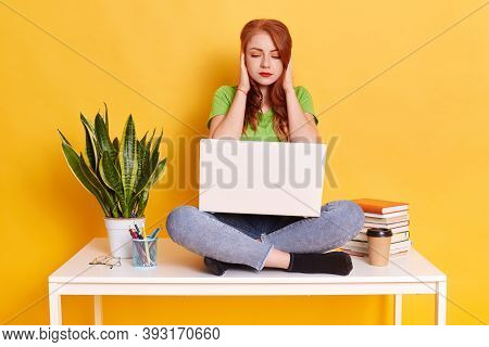 Student Woman Sits On Table With Laptop On Knees, Covering Ears With Palms, Ignoring Annoying Loud N