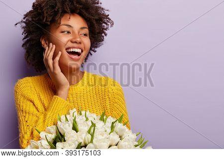 Overjoyed Pleasant Looking Dark Skinned Woman With Curly Hair, Gazes Aside, Keeps Hand On Cheek, Smi