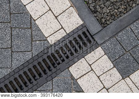 Concrete Bricks In Two Different Colors And Residential Driveway Water Drain Close Up. Architectural