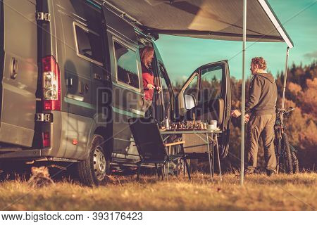 Caucasian Couple And Their Weekend Getaway. Camper Van Rv Boondocking In Remote Place During Scenic