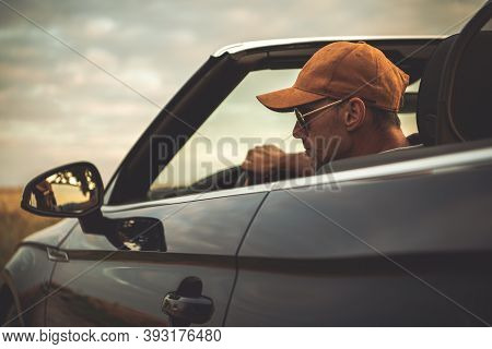 Caucasian Men In His 40s Wearing Baseball Cap Driving His Convertible Car With Roof Opened During Su