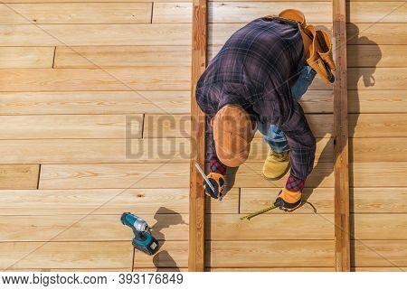 Caucasian Worker Building Wooden Deck For His Backyard Garden. Top View.