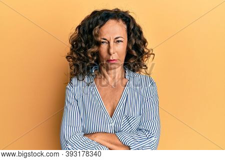 Middle age hispanic woman wearing casual clothes skeptic and nervous, disapproving expression on face with crossed arms. negative person.