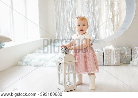Pretty Little Girl In Cute Dress With Pink Bow Looking Like A Little Princess, Standing Near White W