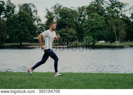 Full Length Shot Of Fast Male Runner Runs Along River, Enjoys Speed, Photographed In Motion, Dressed